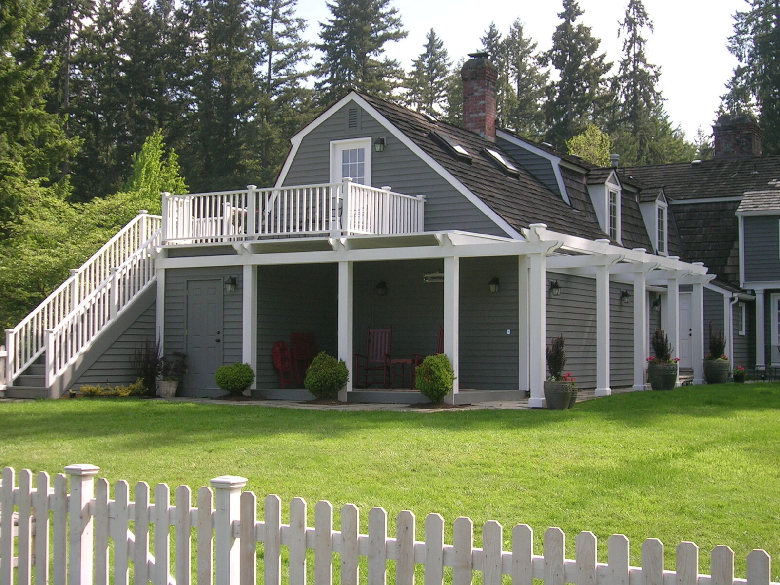Large gray home with with deck on the back of the house